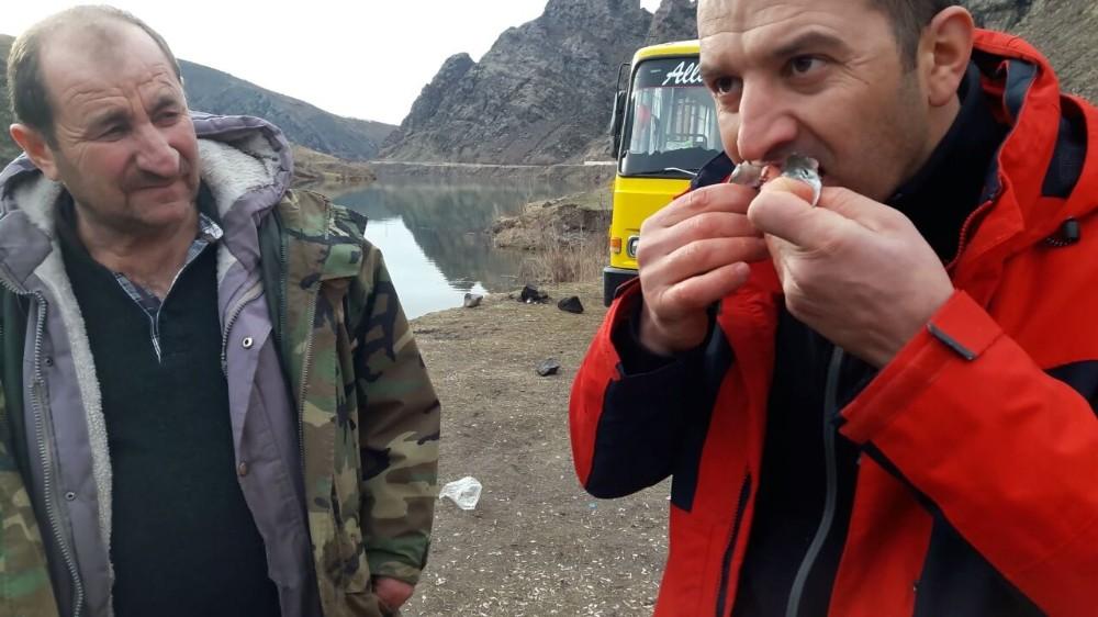 Barajda tuttuğu balığı çiğ yedi