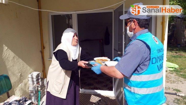 Din görevlisi belde de yaşayan yaşlılara iftar yemeği dağıtıyor