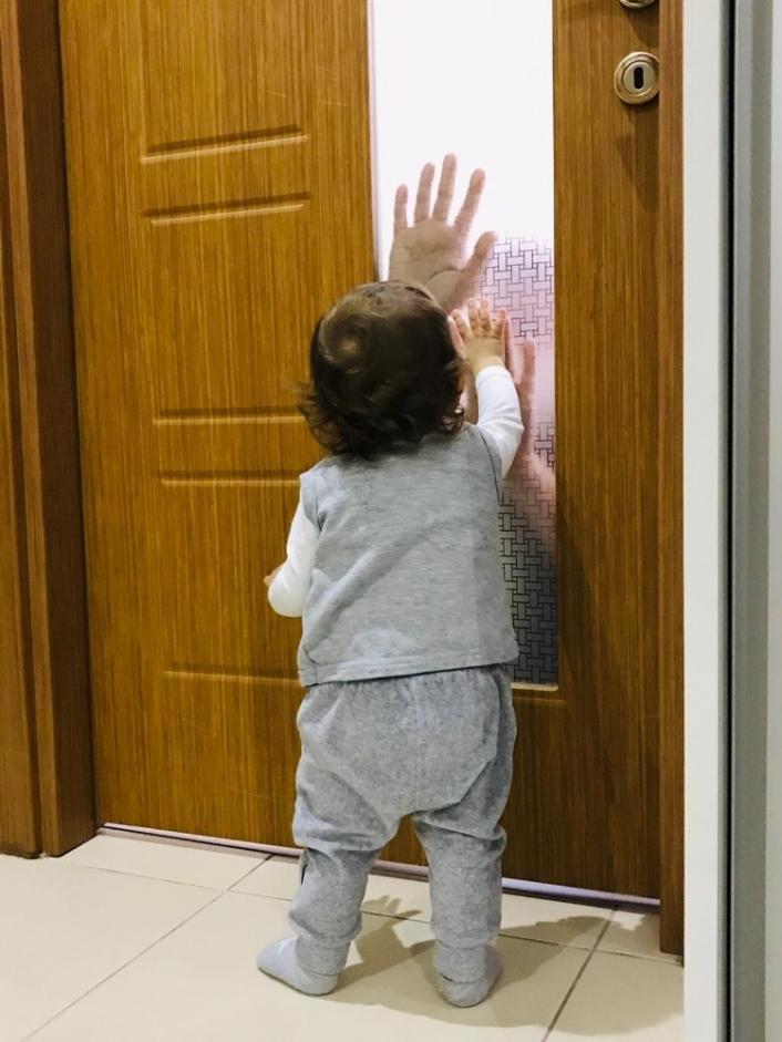 Koronalı baba çocuğunu camın arkasından seviyor